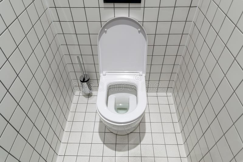 New clean toilet, with modern design and white ceramic toilet bowl against light tiles royalty free stock photos