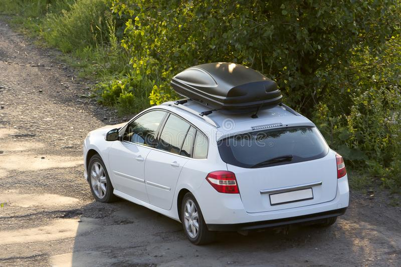 New clean white modern car with black roof luggage box container moving along empty asphalt road in bad condition by green trees a stock image