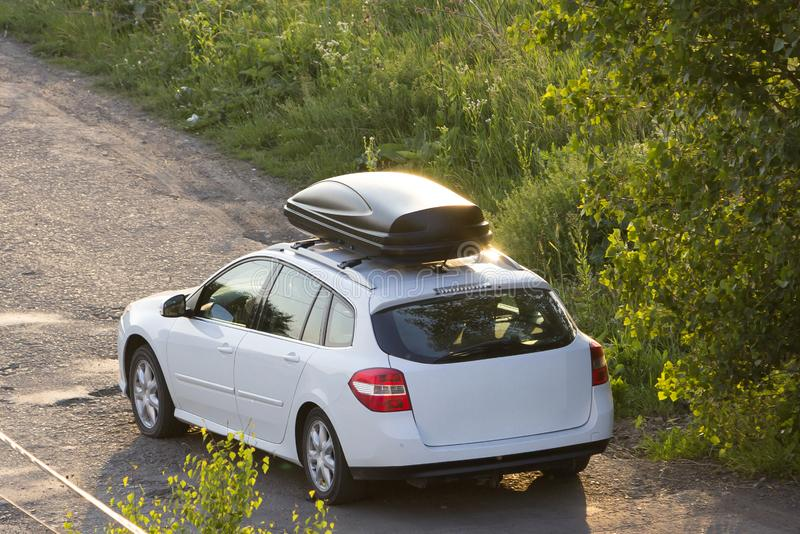 New clean white modern car with black roof luggage box container moving along empty asphalt road in bad condition by green trees stock images