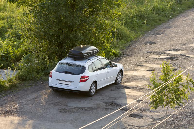 New clean white modern car with black roof luggage box container moving along empty asphalt road in bad condition by green trees royalty free stock photography