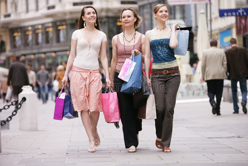 New clothes. Mother and her two daughters shopping stock photos