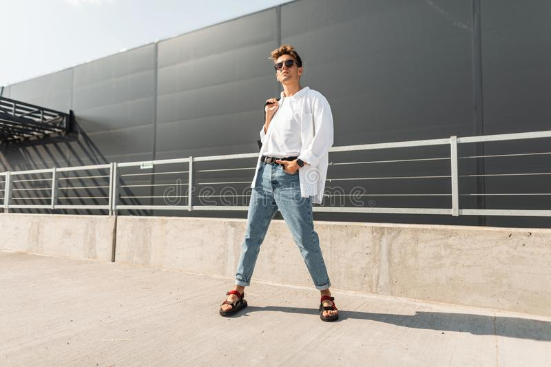 New collection of fashionable summer menswear. Attractive young hipster man in stylish clothes in vintage sunglasses. With a hairstyle with a bag in sandals royalty free stock photo