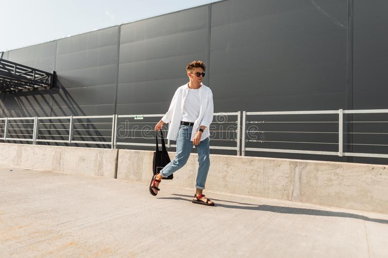 New collection of stylish summer menswear. Handsome young hipster man in fashionable clothes in vintage sunglasses. With a hairstyle with a bag in sandals poses royalty free stock photography