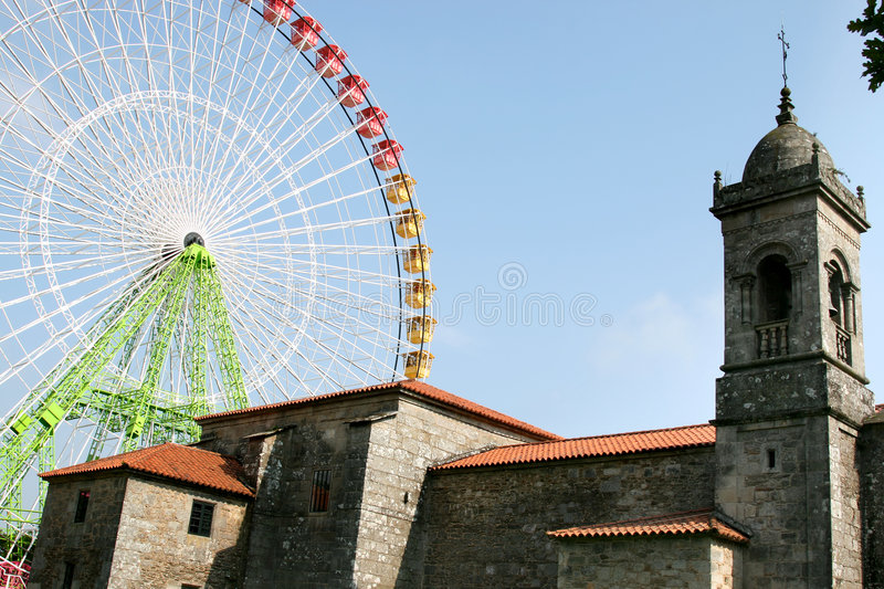 New colourful Ferris wheel and old spanish church. A modern large Ferris wheel in rainbow colours in the place of pilgrimage Santiago de Compostela in Spain stock images