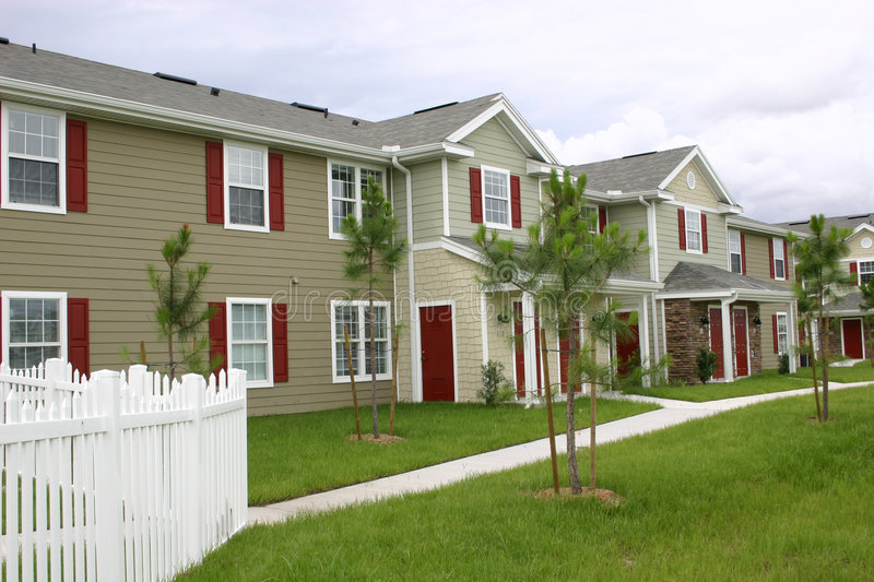 New Condominium village. Consisting of attractive condos with red shutters and doors and trimmed in white, sidewalks and beginning of landscaping stock photography