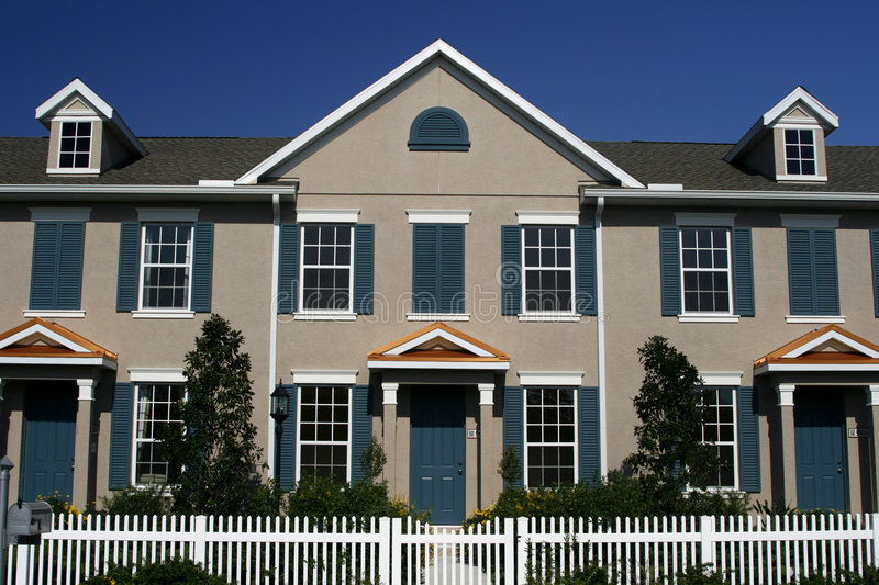 New Condos with Picket Fence. Front view of new condos with white picket fence, blue shutters and doors, French windows, and white trim, against bright blue sky royalty free stock images
