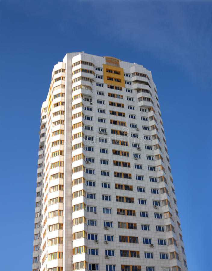 New constructed building over clear blue sky. Front view of high new constructed residential building over clear blue sky vertical view stock photography
