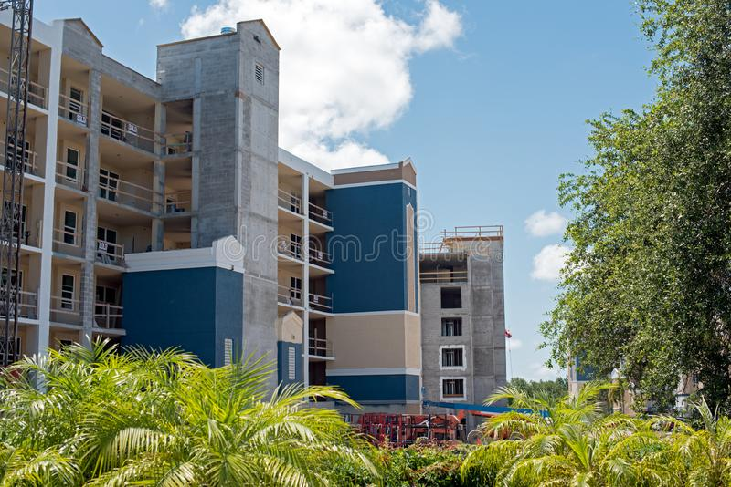 New construction of apartment homes. With freshly installed windows. Building is half painted and shows many SOLD signs stock photos