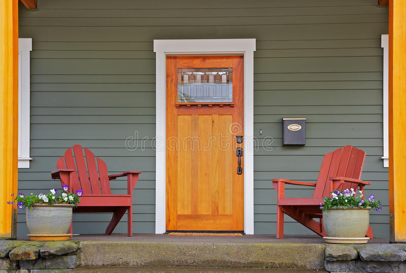 New craftsman Home front. Mission style Stained wood front door with beveled glass surrounded by two Adirondack chairs and flowers stock photo