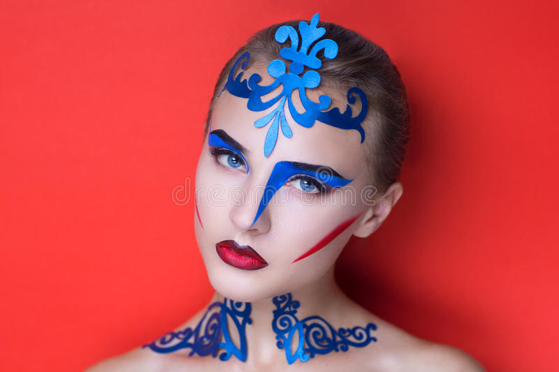 New crazy art. Portrait of beautiful young girl lady model woman. Fashionable absurd look. Fantasy creative makeup geometric style Cubism. Expressive blue royalty free stock image