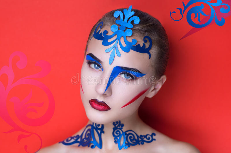 New crazy art. Portrait of beautiful young girl lady model woman. Fashionable absurd look. Fantasy creative makeup geometric style Cubism. Expressive blue stock photography