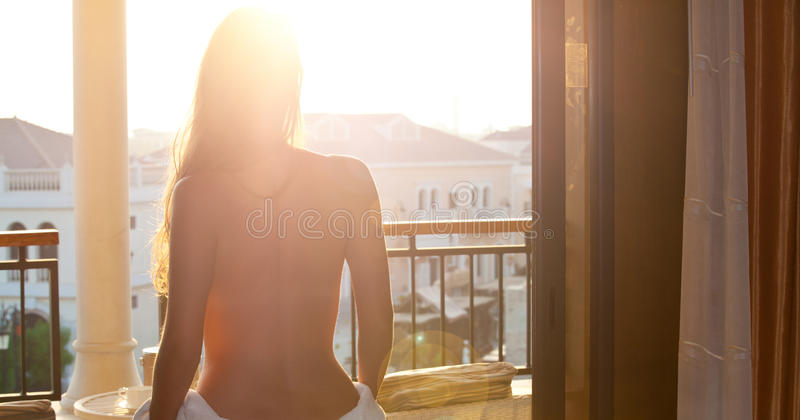 New day, new possibilities. Beautiful woman wearing white towel, watching the sunrise. New day, new possibilities stock photo