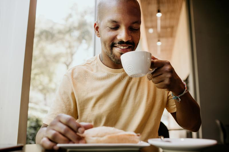 New day welcome.Young attractive African man enjoying his morning coffee and french croissant while sitting at modern royalty free stock photo