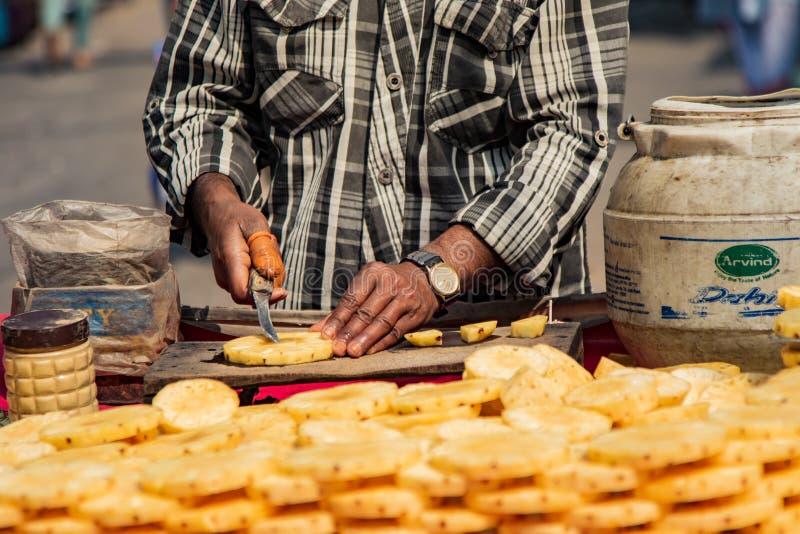 New Dehli, la India, el 19 de febrero de 2018: El hombre prepara la piña para la venta foto de archivo libre de regalías