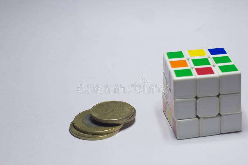 New Delhi, India - November 10, 2019. Coins And Rubik's cube on white background with space. For text, symbol, sign, object, problem, random, construction royalty free stock photo