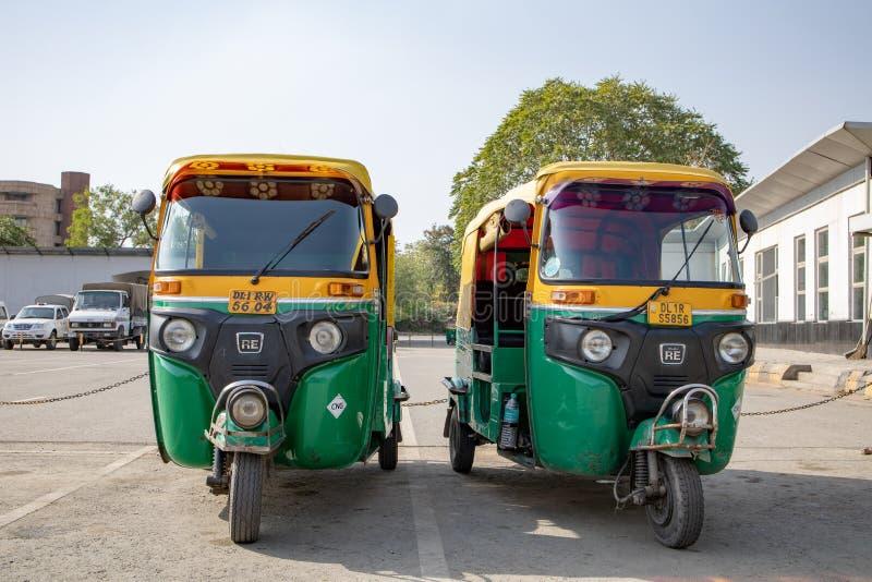 New Delhi Indien - April 2019: Den klassiska automatiskrickshawen Indien Tuk Tuk med person som drar en skottkärra tre är den lok arkivfoton