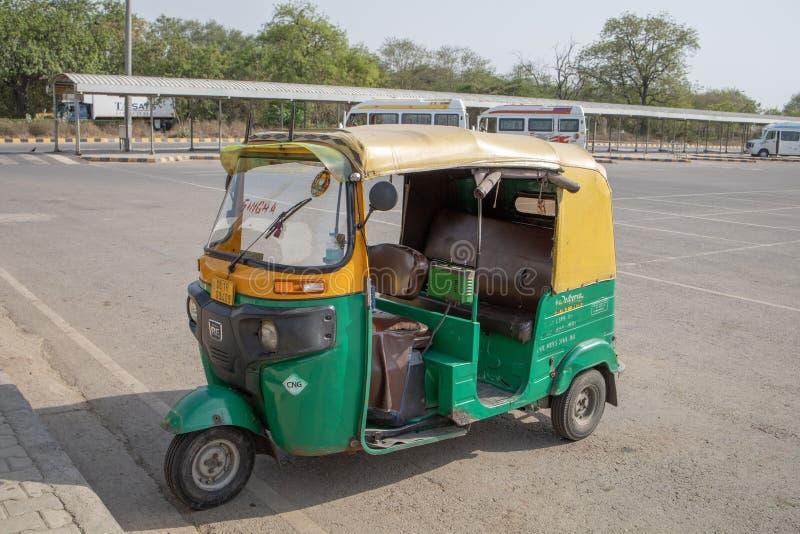 New Delhi Indien - April 2019: Den klassiska automatiskrickshawen Indien Tuk Tuk med person som drar en skottk?rra tre ?r den lok arkivbilder