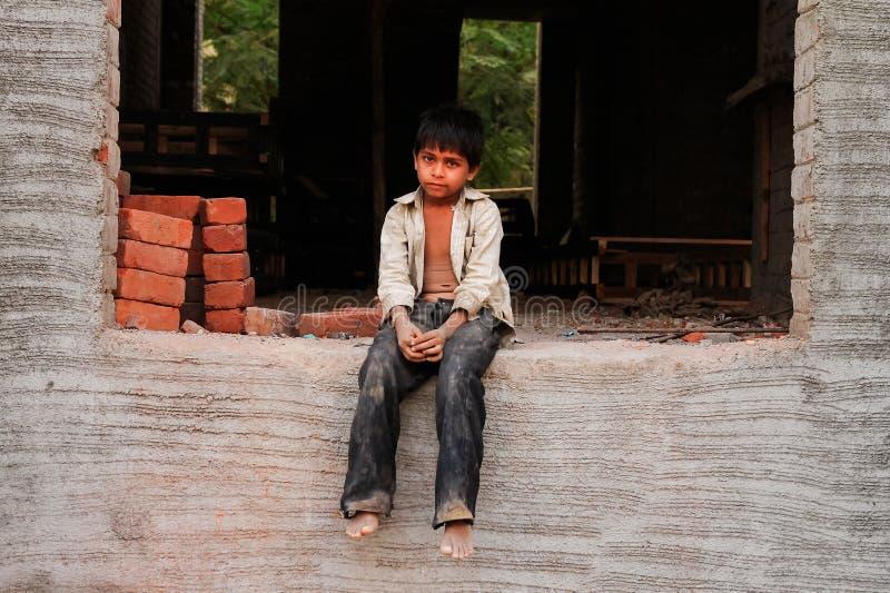 New Delhi Indien - 20 oktober 2017: stående av den ledsen unga indiska pojken som arbetar som murare i konstruktion med smutsig k royaltyfria bilder