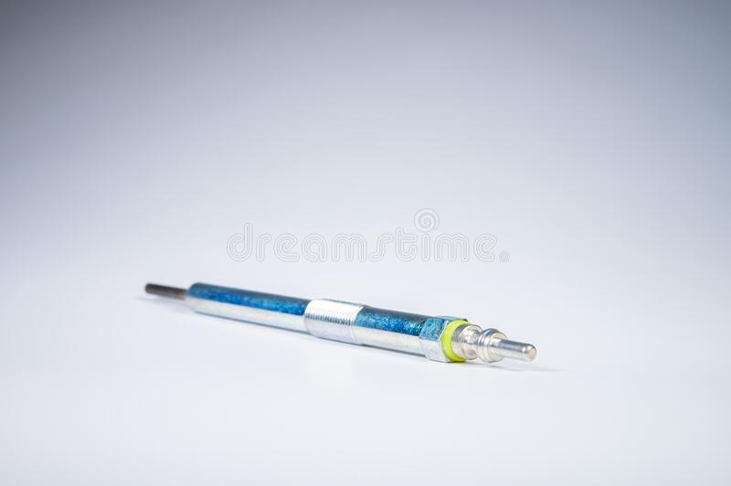 New diesel engine glow plug on a gray background. The concept of new spare parts for diesel internal combustion engines.  royalty free stock photos