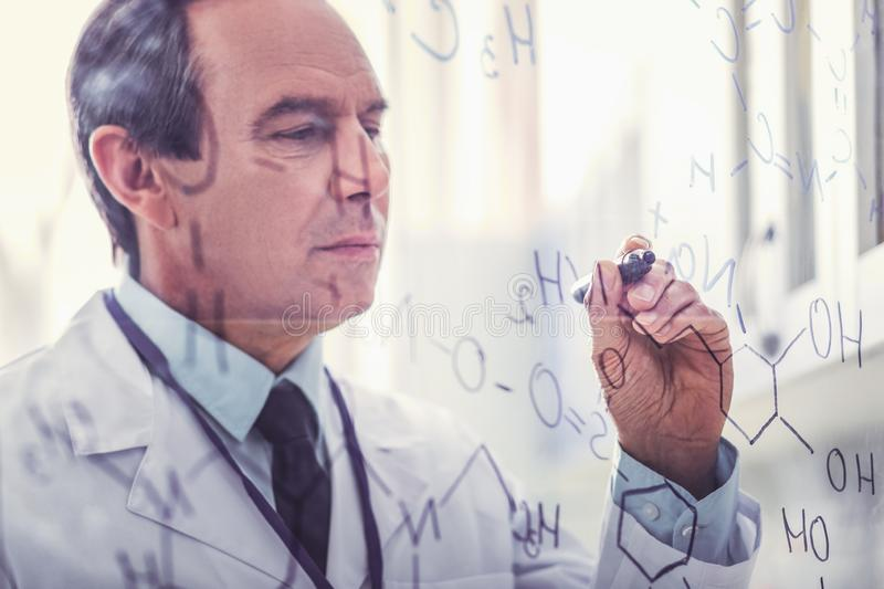 Chemist creating molecular chain for new discovery. New discovery. Professional chemist feeling satisfied while creating long molecular chain for new discovery stock photography