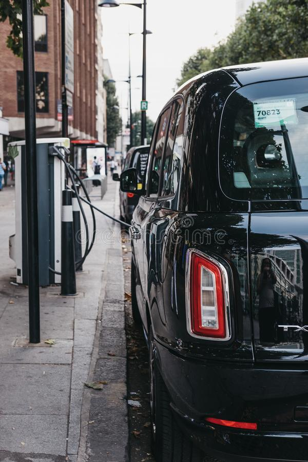 New electric LEVC TX London black cab charging from changing point in London, UK. royalty free stock photography