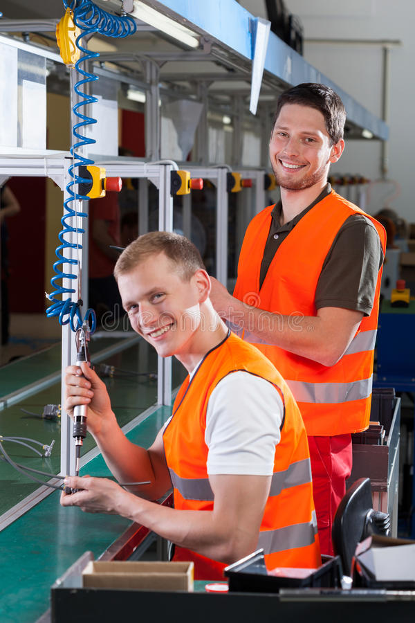 New employee on the production line. Factory worker teaching new employee how to work on the production line royalty free stock photo