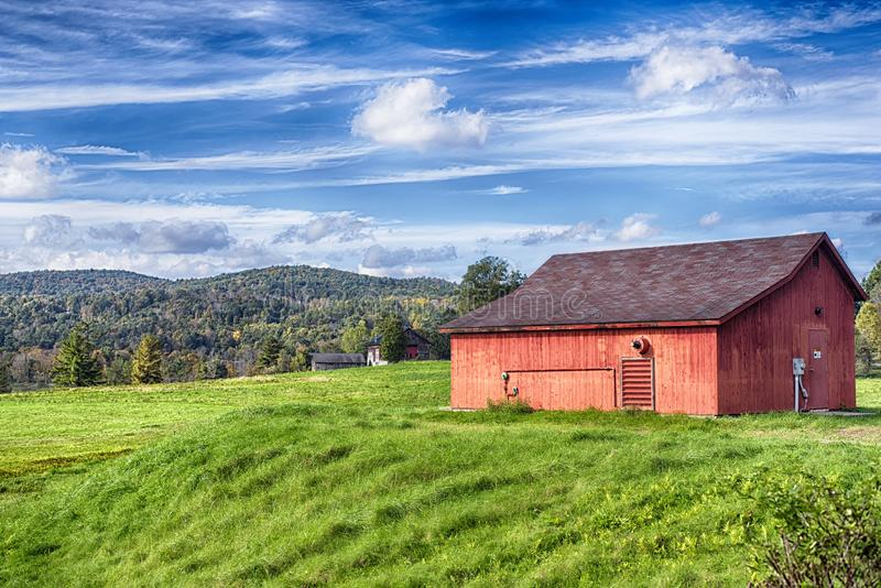 New england red barn landscape. A red barn on a field landscape in the new england town of Cornwall connecticut on a blue sky day stock image