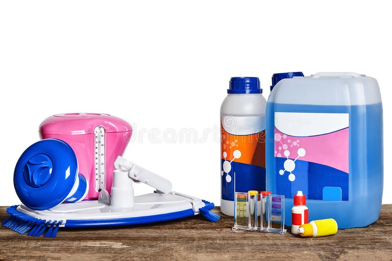 Equipment with chemical cleaning products and tools for the maintenance of the swimming pool on a wooden surface against. New equipment with chemical cleaning royalty free stock photography