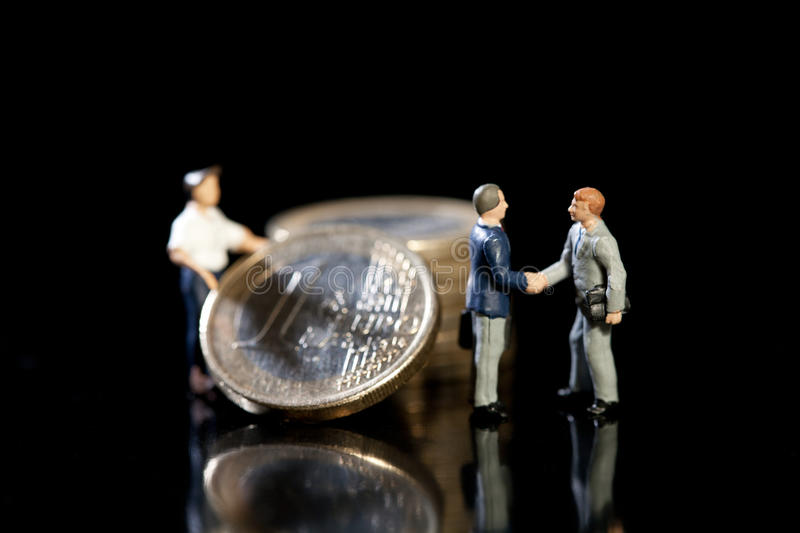 New Euro Economic Strategy. Two miniature toy model businessmen shake hands standing in front of a pile of Euro coins and workman, symbolic of new economic stock photo