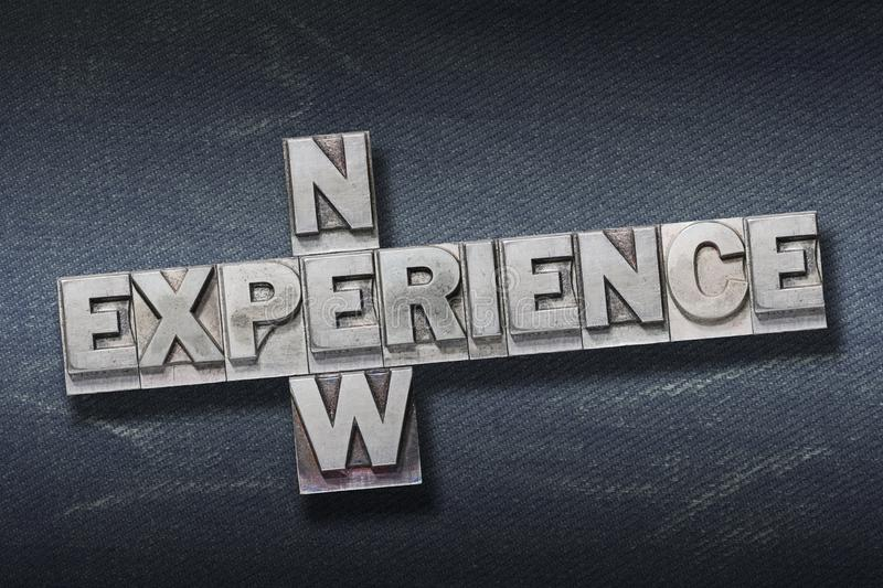 New experience den. New experience crossed phrase made from metallic letterpress on dark jeans background stock photos