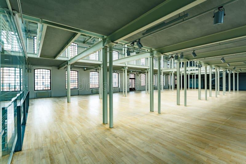 New factory hall with pillars. Wood floor and loft windows stock image