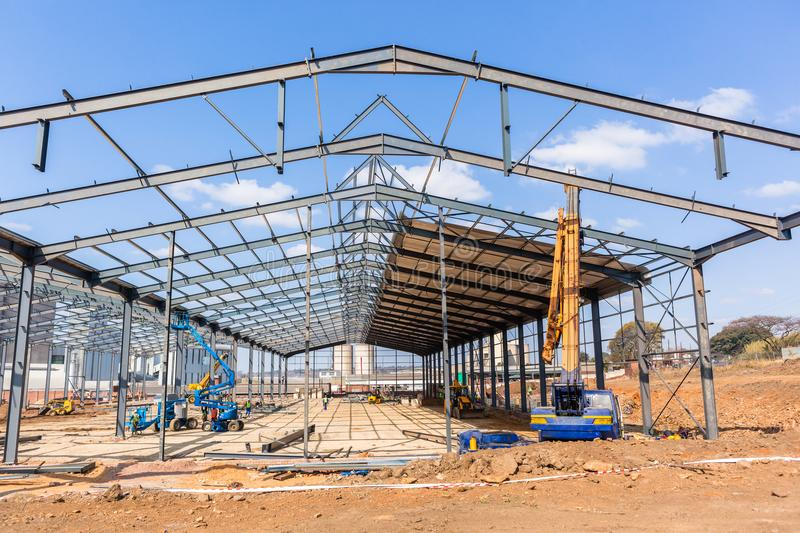 New Factory Steel Structure Construction. New factory large warehouse construction steel beams frames assembled halfway to completion of frame structure stock photo