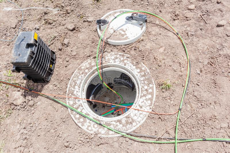 New Fiber Optic Cables Underground Internet Connection Box. Communications construction of new internet fast speed fiber optic cables been installed underground stock image