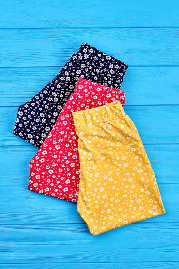 New folded baby girl pants. Setting of colorful baby girl leggings, vertical image. Modern kids apparel on sale stock photos