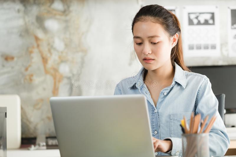 New generation asian business woman using laptop at office, Asian women sitting while working, mobile office concept. New generation asian business woman using stock photography