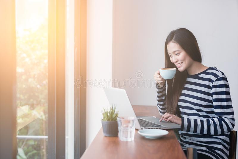 New generation asians business woman using laptop at coffee shop. Asian woman sitting smiling while working on mobile office concept stock photo