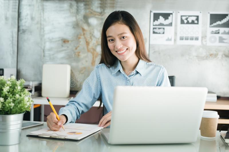 New generation asians business woman using laptop at office, Asia. N woman sitting smiling while working on mobile office concept stock photos