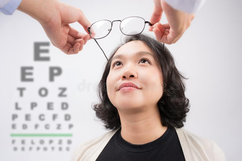 New glasses. Optometrist giving asian woman eyeglasses to try stock image