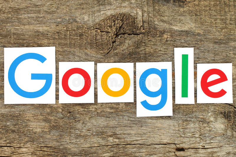 New Google logotype on old wood. Kiev, Ukraine - January 12, 2016:New Google logotype printed on paper, cut and placed on old wood.Google is USA multinational stock photo