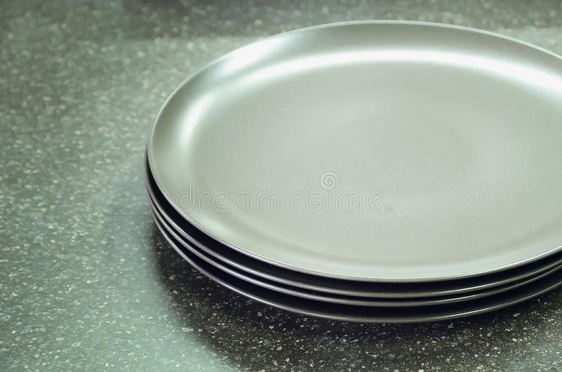 New gray empty plates lie on the table top made of artificial stone. Modern kitchen interior stock photo