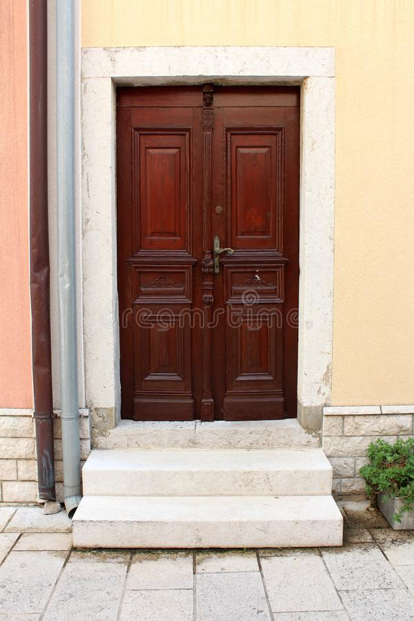New hardwood family house entrance doors with decorative details and baroque style door handle mounted on stone frame wall next to stock photography
