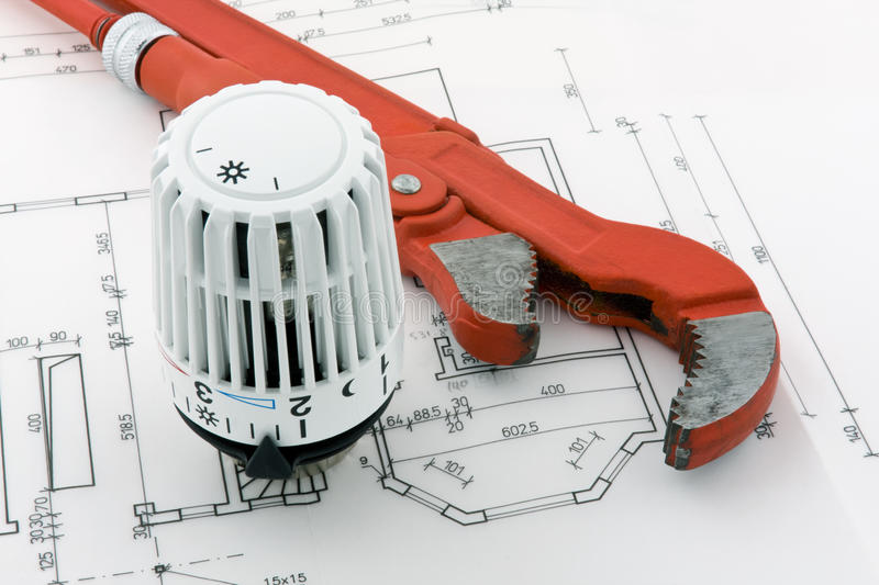 New heating 4. A thermostat for a new heating system is combined with a pipe wrench on a blueprint royalty free stock photography