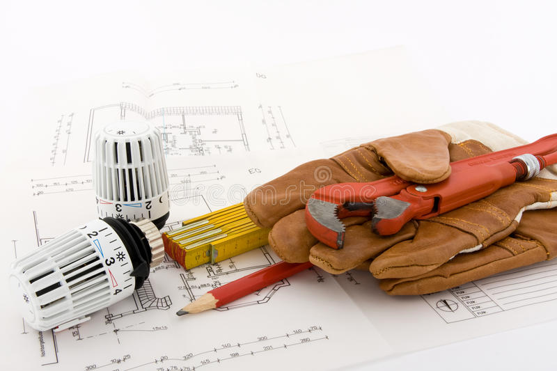 New heating system?. Two thermostats for a new heating are combined with a ruler, a pencil, a pipe wrench and a pair of work gloves on a blueprint stock photo
