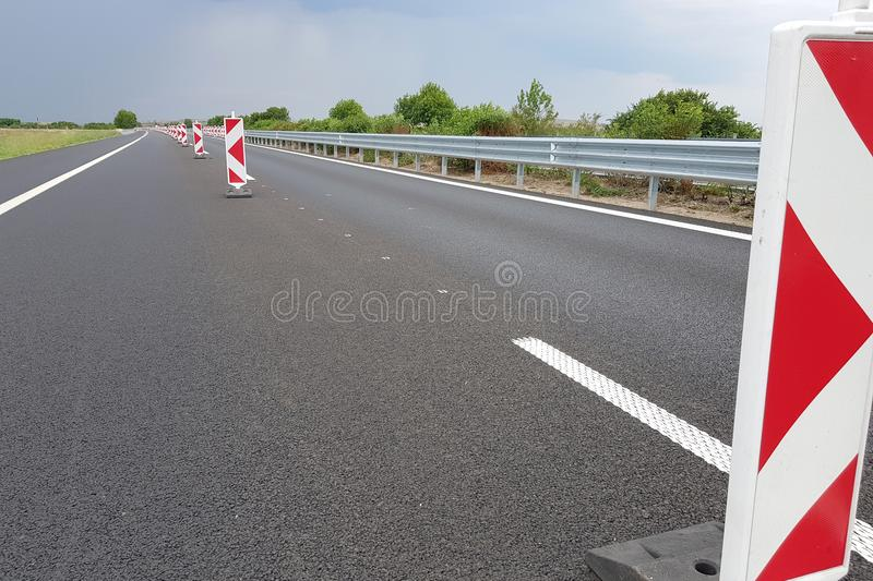 New Highway Lane with Road Signs. New asphalt lane of a highway divided by a many roadwork marks signs stock photography