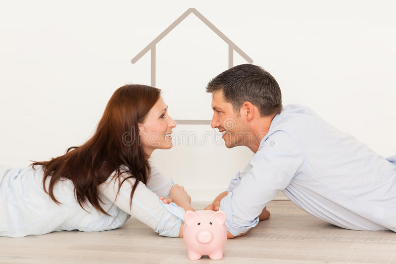 New home. Happy parents dreaming new home with piggy bank for money stock images