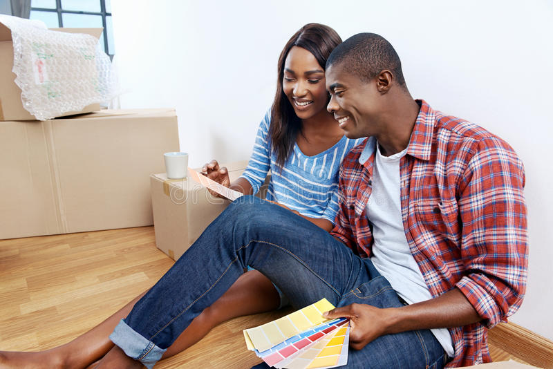 New home choices. Young african couple having fun deciding on paint colour swatch for new home apartment royalty free stock photography