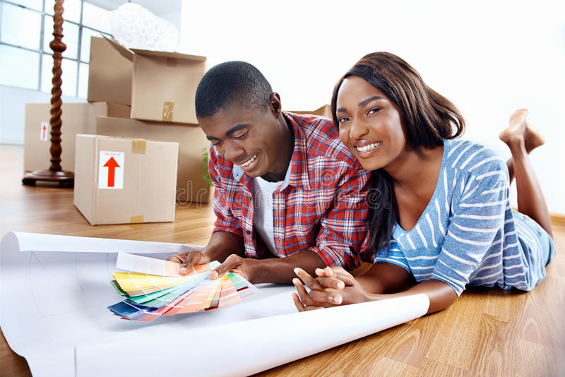 New home choices. Young african couple having fun deciding on paint colour swatch for new home apartment stock photos