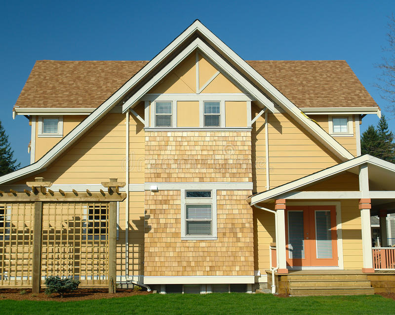 New Home Exterior Yellow Siding. Colourful new home exterior showing bright yellow siding royalty free stock photography