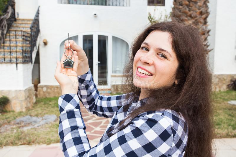 New home, house, property and tenant - Young funny woman holding key in front of her new home after buying real estate stock photography