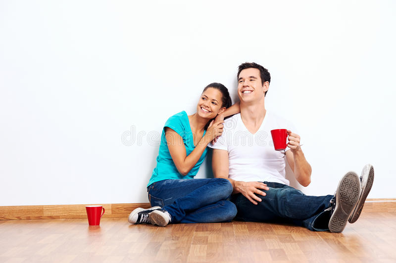 New home mixed couple. Couple moving into empty new home sitting on floor together and drinking coffee